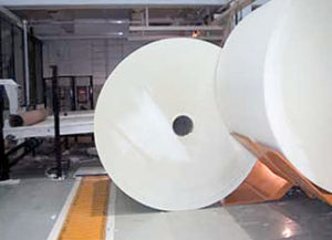Transfer of rolls one by one to floor level slat conveyor